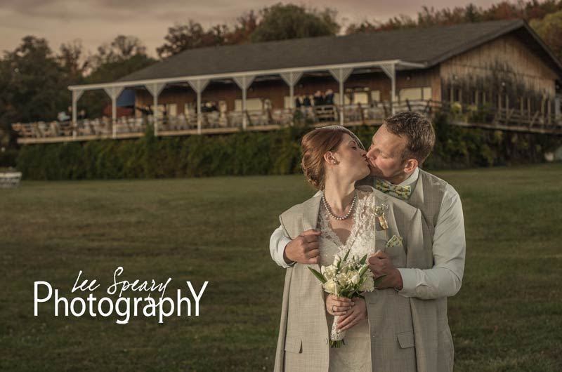 Bride and Groom kissing, cafe in background – Photo credit Lee Speary Photography